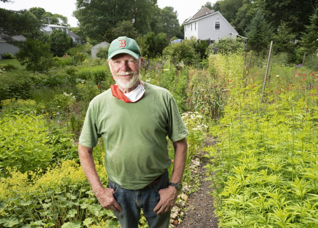 Maine Gardener Tom Atwell poses for a photo in his lush, lovely garden in Cape Elizabeth.