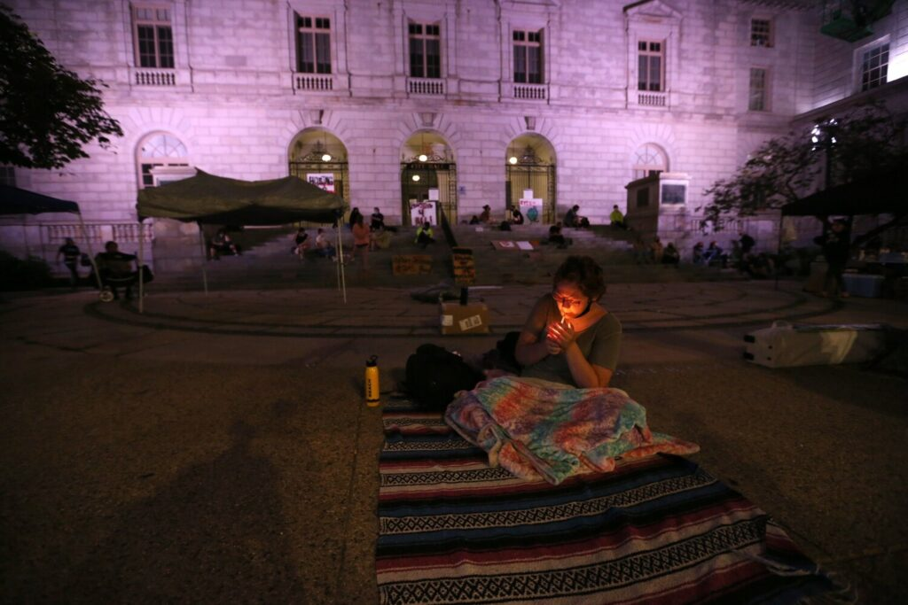 Christan Sark, 19, who is homeless and pregnant, lights a cigarette while sitting on a blanket outside Portland City Hall, where she intended to sleep Wednesday night.