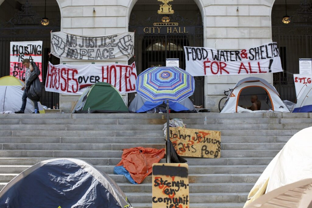 "Tents and protest signs line the top of the steps at Portland City Hall as the so-called ""sleep out"" enters another night."