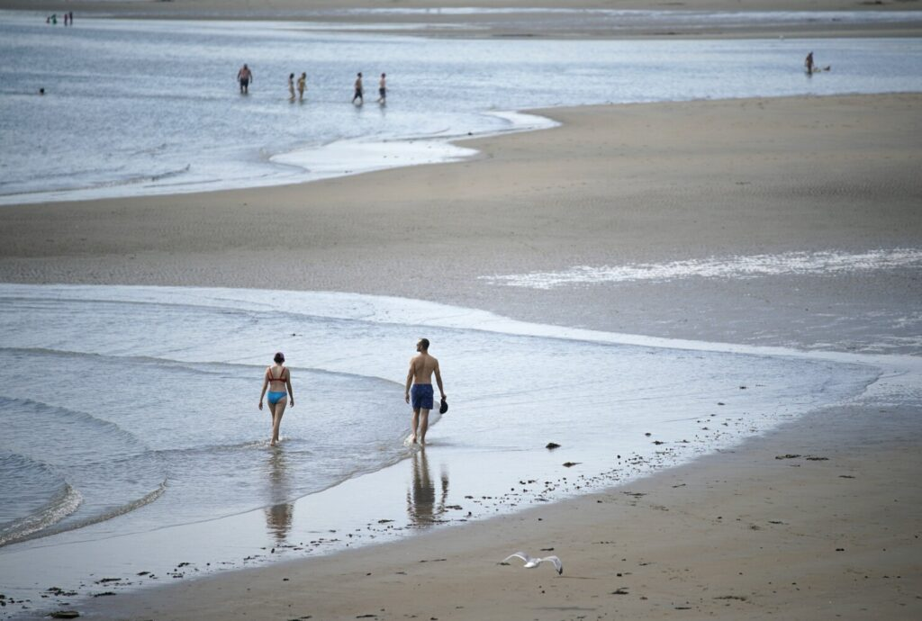 People walk in the shallow water on Thursday at Popham Beach State Park, where bathers were told to only go in the water ankle deep that day because of a recent shark attack and subsequent shark sightings off the Maine coast.