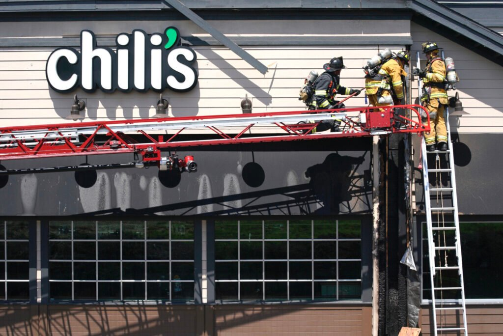 Firefighters work to pull charred pieces of siding and wood from the Chili's restaurant near The Maine Mall in South Portland on Monday. Officials don't yet know the cause of the fire, which they said was brought under control in about 10 minutes.