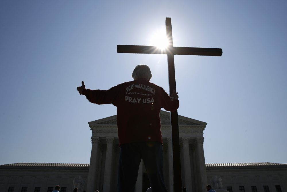 A man holds a cross as he prays prior to rulings on religious school issues outside the Supreme Court in Washington on July 8, 2020. AP Photo/Patrick Semansky