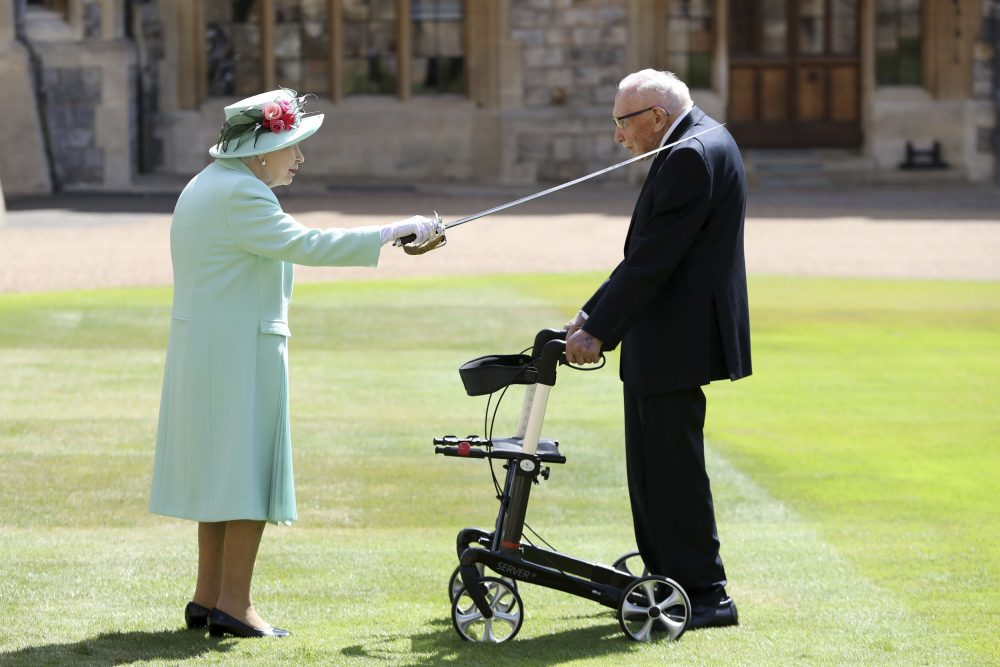 Capt. Sir Thomas Moore receives his knighthood from Britain's Queen Elizabeth during a ceremony at Windsor Castle in Windsor, England, on Friday. Sir Tom raised about $40 million for health service charities by walking laps of his Bedfordshire garden.
