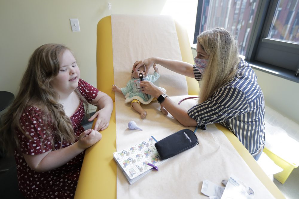 Emilyanne Wade, 12, left, looks on as Tricia Nora, a pediatric nurse practitioner, examines Sophia, Wade's baby doll in a medical clinic at Mary's Place, a family homeless shelter located inside an Amazon corporate building on the tech giant's Seattle campus.