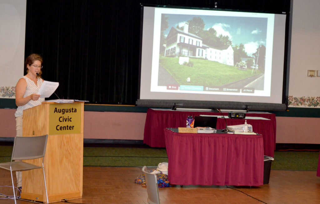 Deputy City Planner Betsy Poulin introduces the Kennebec Historical Society building expansion project with a rendering of the final product in the background.