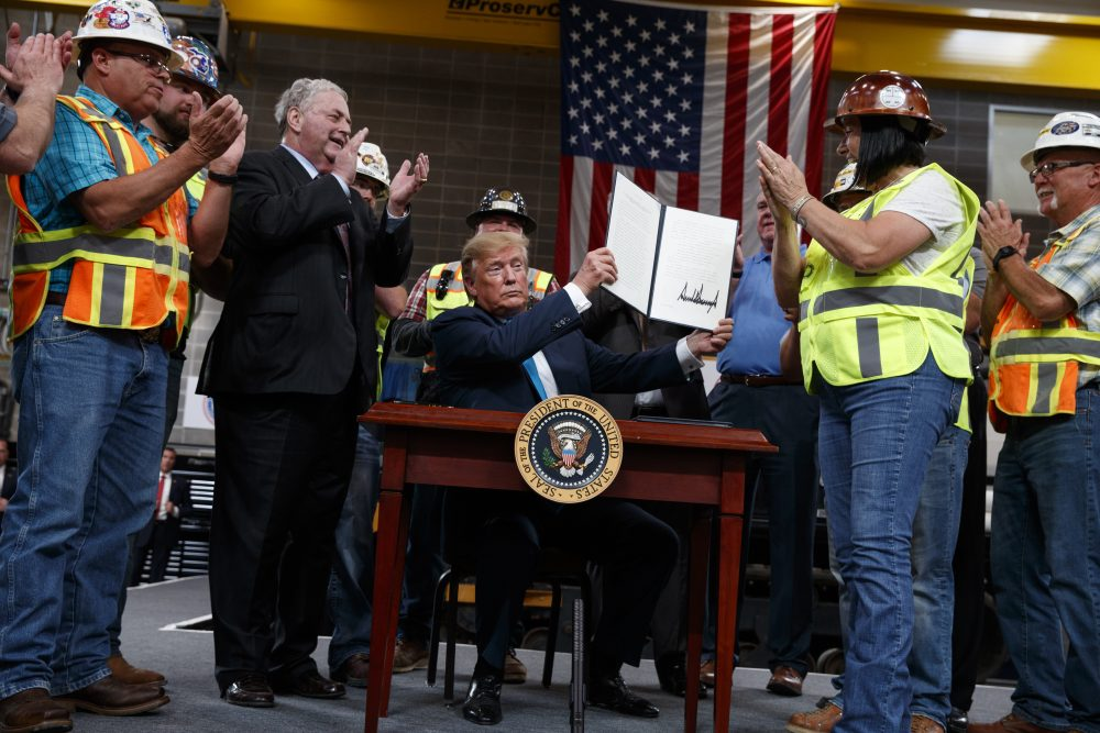 President Trump holds up an executive order on energy and infrastructure after signing it at the International Union of Operating Engineers International Training and Education Center in Crosby, Texas, in 2019. Attorneys general in 20 states and the District of Columbia sued the Trump administration on Tuesday, alleging that new federal rules undermine their ability to protect rivers, lakes and streams within their borders.