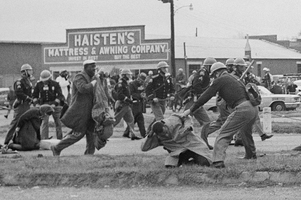 Astate trooper swings a billy club at John Lewis, right foreground, chairman of the Student Nonviolent Coordinating Committee, to break up a civil rights voting march in Selma, Alabama, in 1965. Lewis sustained a fractured skull. Lewis, who carried the struggle against racial discrimination from Southern battlegrounds of the 1960s to the halls of Congress, died Friday.