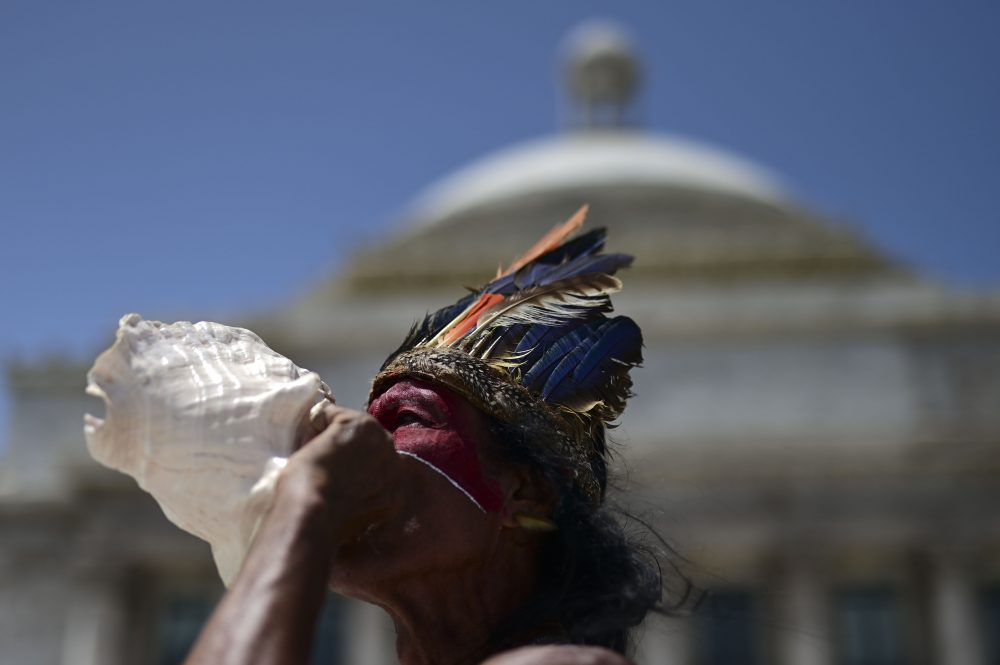 Baracutey blows on a conch shell outside the Capitol building while joining a group of activists demanding statues and street names commemorating symbols of colonial oppression be removed, in San Juan, Puerto Rico on Saturday.