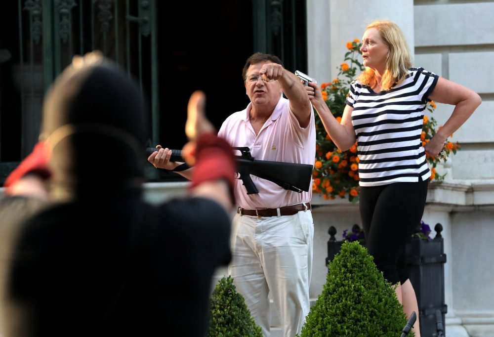 Armed homeowners Mark and Patricia McCloskey, standing in front their house, confront protesters marching to St. Louis Mayor Lyda Krewson's house in the Central West End of St. Louis on June 28. St. Louis' top prosecutor said Monday she is charging the couple with felony unlawful use of a weapon.
