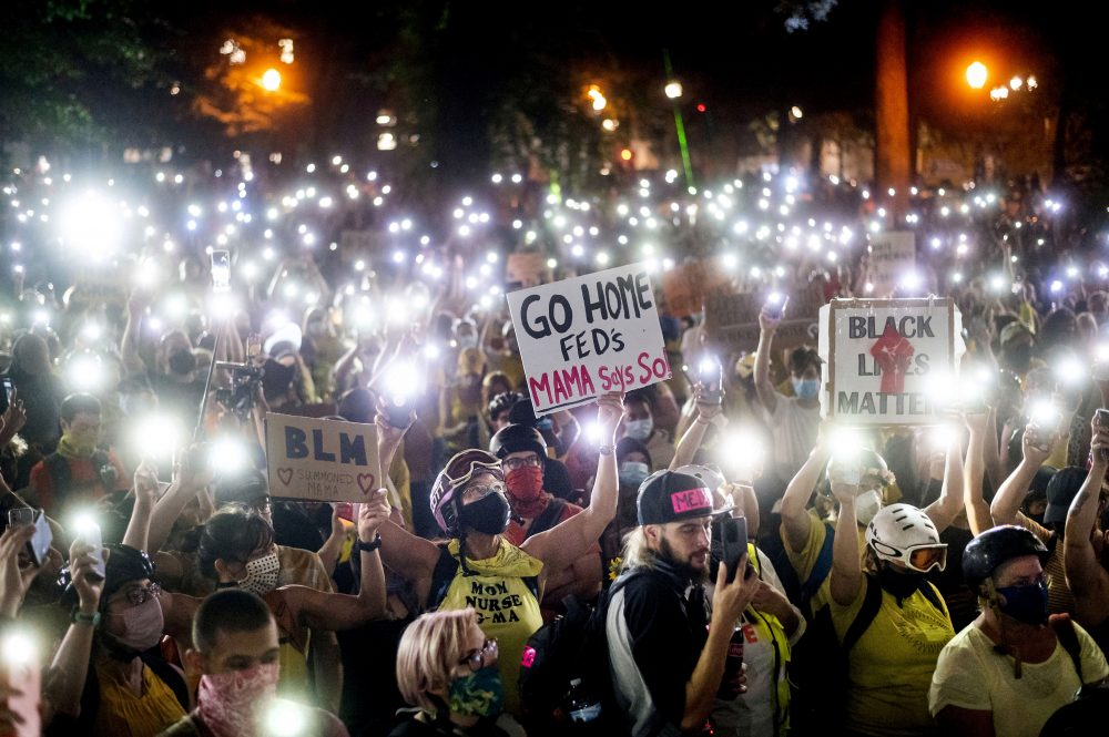 Hundreds of Black Lives Matter protesters hold their phones aloft on Monday in Portland, Ore. Federal officers' actions at protests in Oregon's largest city, hailed by President Trump but done without local consent, are raising the prospect of a constitutional crisis – one that could escalate as weeks of demonstrations find renewed focus in clashes with camouflaged, unidentified agents outside Portland's U.S. courthouse.