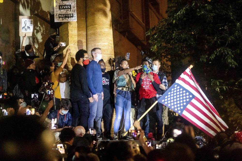 Black Lives Matter organizer Teal Lindseth, 21, addresses protesters as Portland Mayor Ted Wheeler, left, listens on Wednesday in Portland, Ore. Late Wednesday Wheeler joined protesters at the front of the crowd and was hit with chemical irritants several times by federal officers dispersing demons