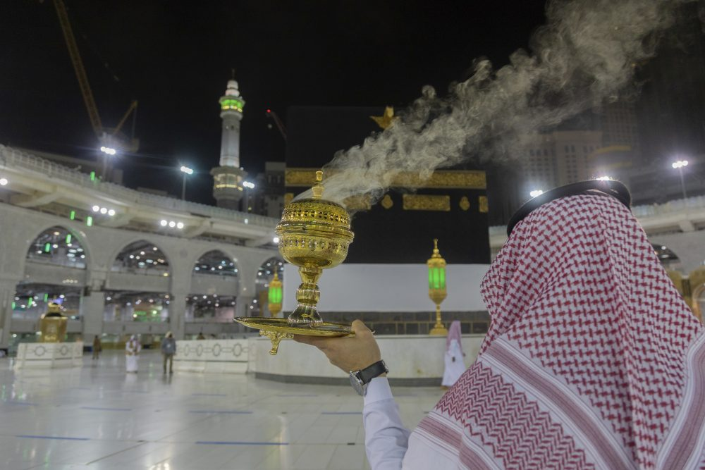 A man burns incense as the area around the Kaaba, the square structure in the Great Mosque, toward which believers turn when praying, is prepared for pilgrims, in Mecca, Saudi Arabia, late Sunday.