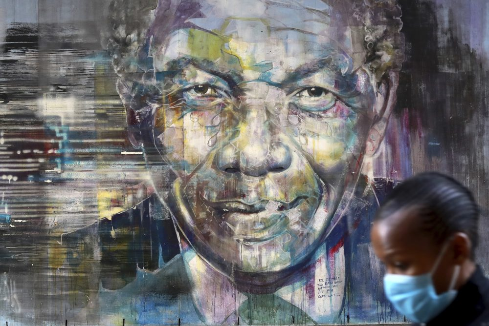 A woman walks past a mural of former President Nelson Mandela in Cape Town, South Africa, on Saturday, as the country celebrates International Mandela Day. Mandela's fight for freedom and human rights makes him the most influential person among Africa's youth, according to a survey conducted across the continent.