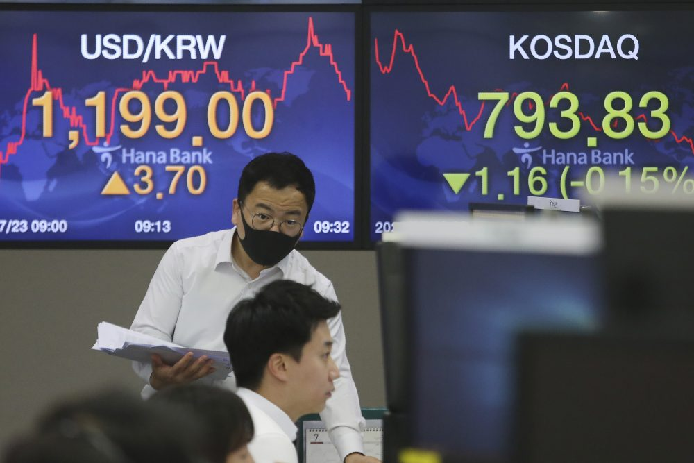 A currency trader talks with his colleague at the foreign exchange dealing room of the KEB Hana Bank headquarters Thursday in Seoul, South Korea. Shares were mixed in Asia on Thursday, with the region's biggest market in Tokyo closed for a four-day weekend.