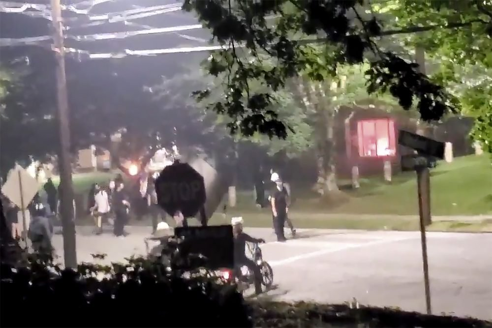 The building, seen right in the background, that houses Georgia State Patrol headquarters was vandalized in Atlanta on Sunday. Video showed protesters appearing to set off at least one firework inside the building.
