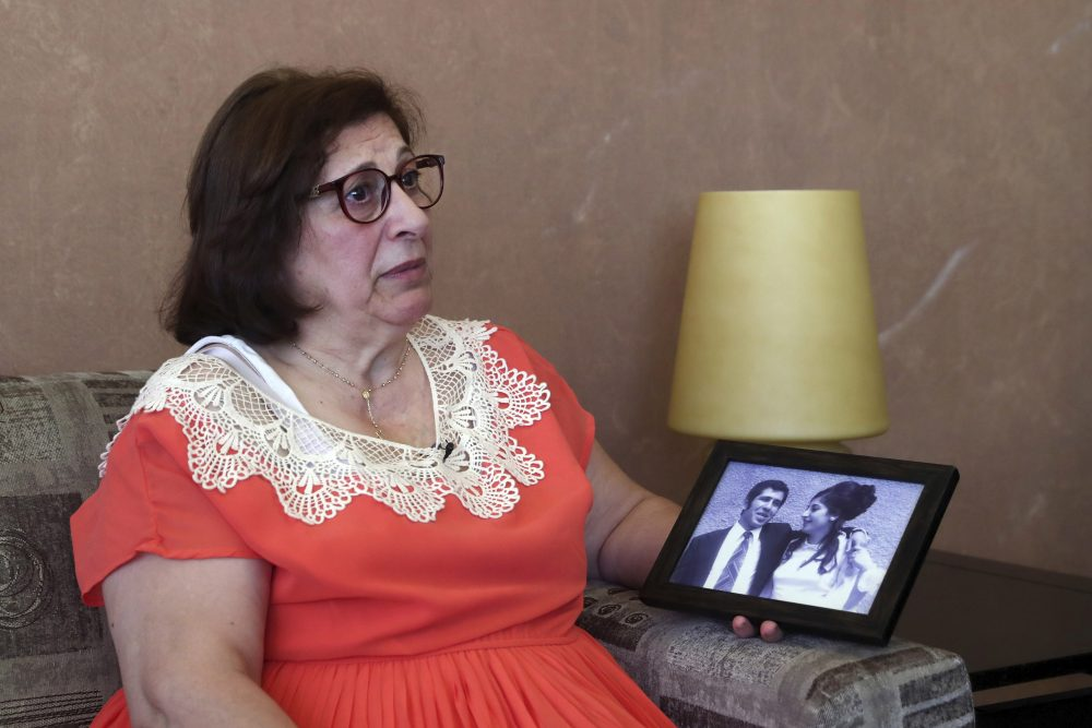 Laure Ghosn, whose husband Charbel Zogheib has been missing for the past 37 years, speaks as she holds their wedding portrait during an interview at her home in Sarba, north of Beirut, Lebanon.