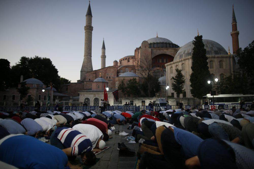 Muslims offer their evening prayers outside the Byzantine-era Hagia Sophia, one of Istanbul's main tourist attractions in the historic Sultanahmet district of Istanbul, following Turkey's Council of State's decision Friday
