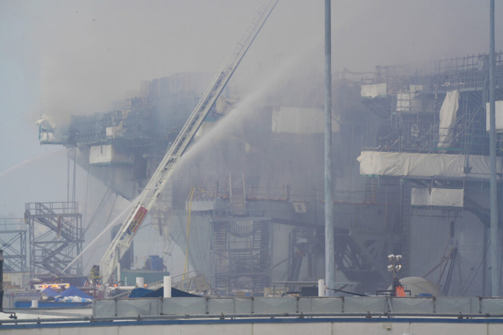 A fire continues to burn more than 24 hours later, aboard Bonhomme Richard at San Diego Naval Base on Monday.