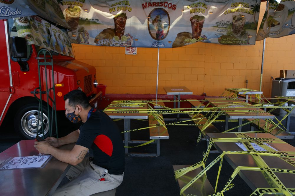 Abel Gomez waits for his order at Mariscos Linda food truck on July 1 as dining tables are sealed off with caution tape due to the coronavirus pandemic in Los Angeles. California Gov. Gavin Newsom extended the closure of bars and indoor dining statewide and has ordered gyms, churches and hair salons closed in most places as coronavirus cases keep rising.