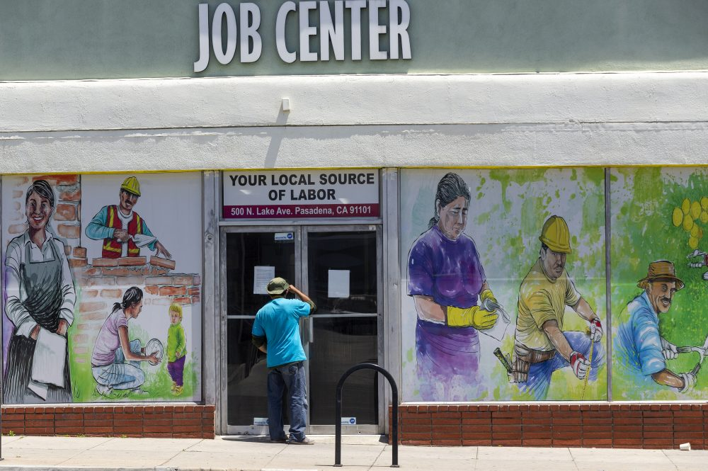 A person looks inside the closed doors of the Pasadena Community Job Center May 7 in Pasadena, Calif.