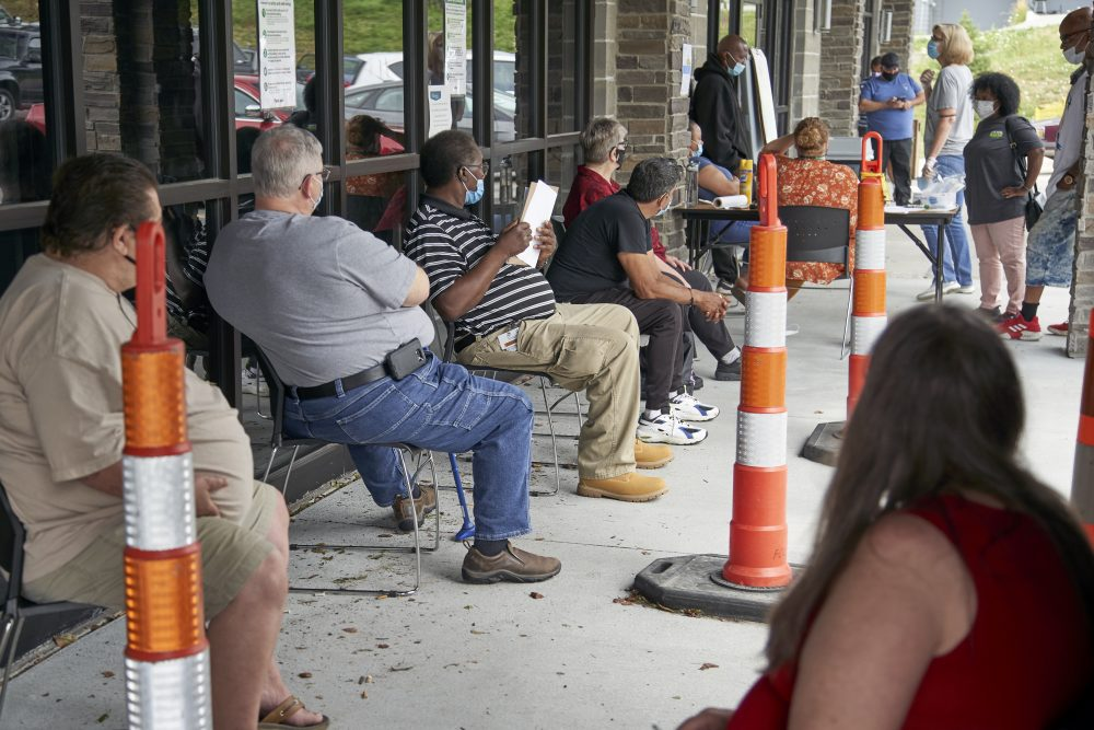 Job seekers wait to be called into the Heartland Workforce Solutions office on July 15 in Omaha, Neb. A Republican proposal to slash the $600 weekly benefit boost for those left jobless because of the coronavirus shutdown could result in weeks or even months of delayed payments in some states.
