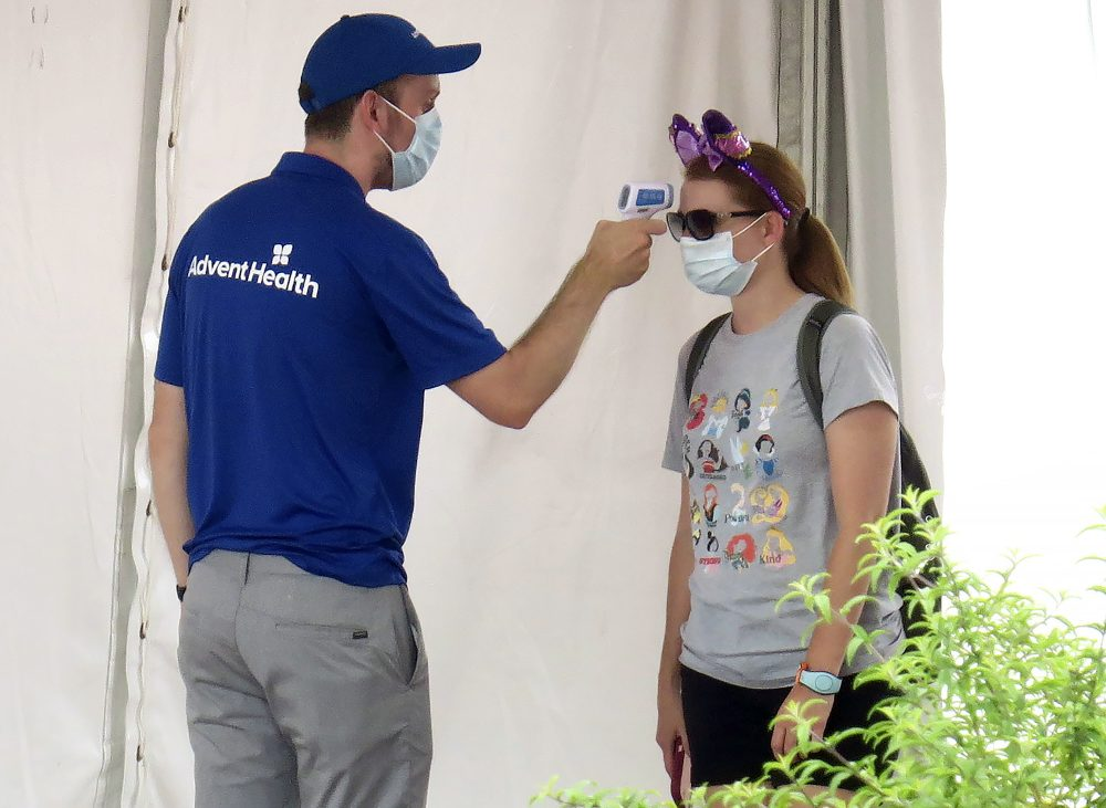 A person gets her temperature taken before entering the official reopening day of the Magic Kingdom at Walt Disney World on Saturday.
