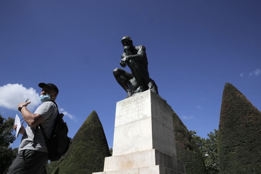 """A visitor walks past """"Le Penseur"""" (The Thinker) by French sculptor Auguste Rodin in Paris. The Musee Rodin can sell 12 bronze replica editions to help offset the cost of the pandemic."""