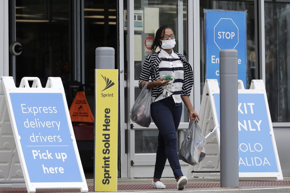 A shopper wears face masks as she leaves a Walmart retail store in Vernon Hills, Ill., Thursday, July 30.