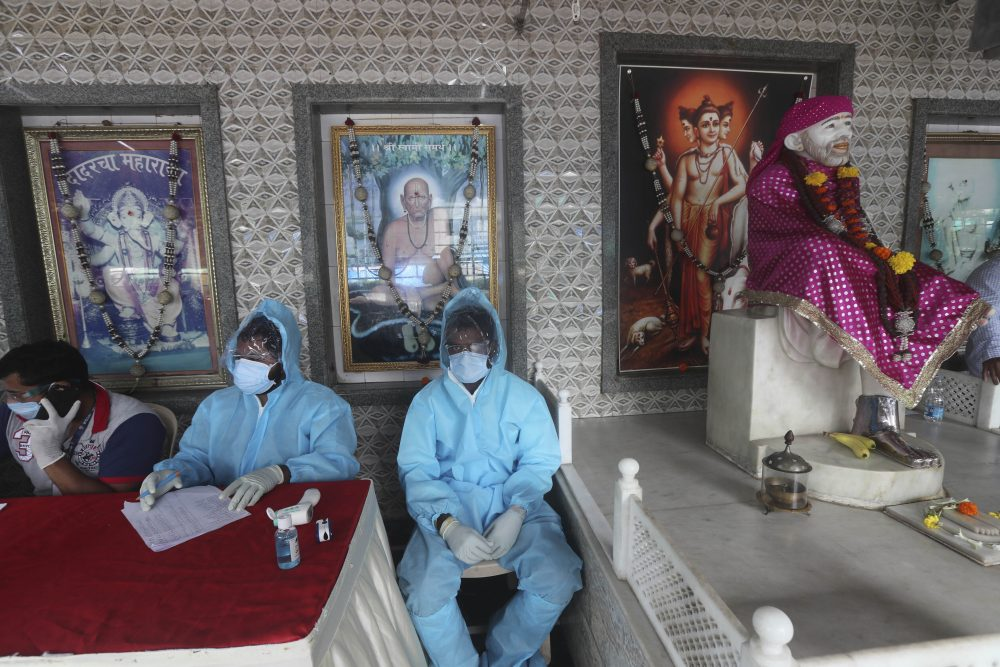 Health workers wait to screen people for COVID-19 symptoms at a temple in Mumbai, India, on Saturday,. India passed 1 million coronavirus cases on Friday, third only to the United States and Brazil.