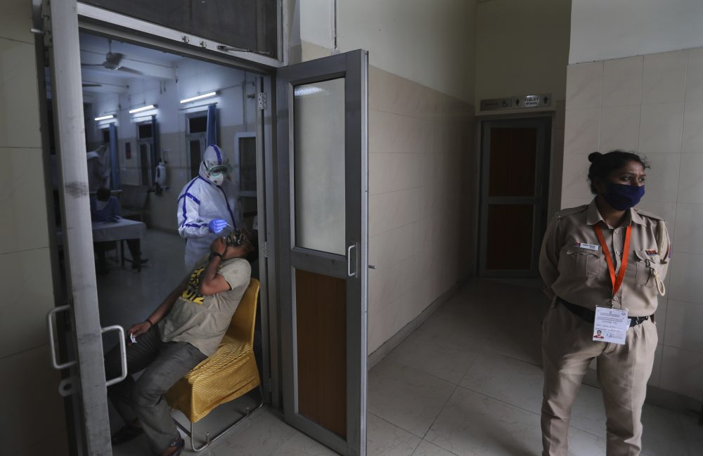 A health worker takes a nasal swab of a person for COVID-19 test as a policewoman stands guard at a local dispensary Saturday in New Delhi, India. India has overtaken Russia to become the third worst-affected nation by the coronavirus pandemic.