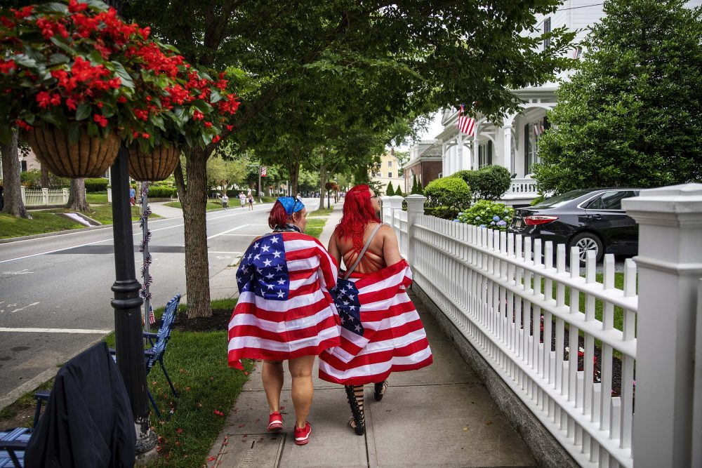 Parade goers draped in American flags walk down the street before a Fourth of July parade begins Saturday in Bristol, R.I. The town, which lays claim to the nation's oldest Independence Day celebration in the country, held a vehicle-only scaled down version of its annual parade Saturday due to the coronavirus pandemic.
