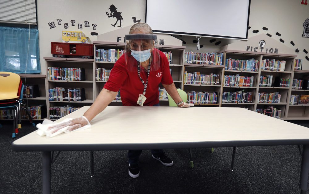 Garland Independent School District custodian Camelia Tobon wipes down a table in the library at Stephens Elementary School in Rowlett, Texas, on Wednesday.