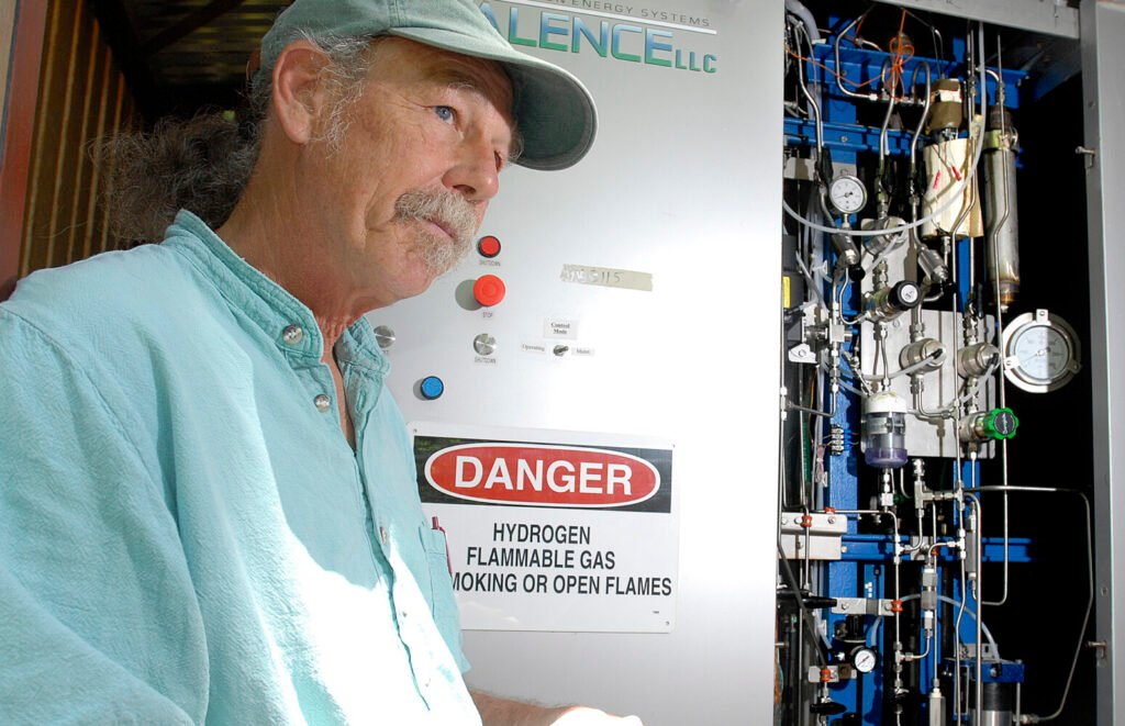 Peter Arnold, project director of Chewonki's  Renewable Hydrogen Project, stands beside the  hydrogen powered back-up electrical system in 2008.