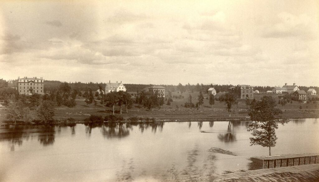 """A photo, circa 1890, captioned """"Maine State College, looking North from Orono."""" Buildings visible include (from left to right) Oak Hall, White Hall (later renamed Wingate), Fernald Hall, Coburn Hall."""