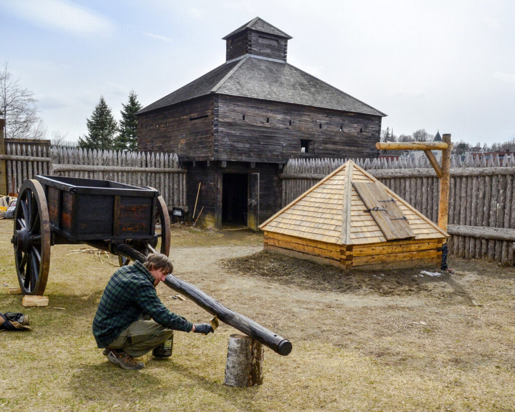 Hannes Moll paints an ox cart with boat soup, a mixture of pine tar, boiled linseed oil and turpentine, in 2018 at Old Fort Western in Augusta.