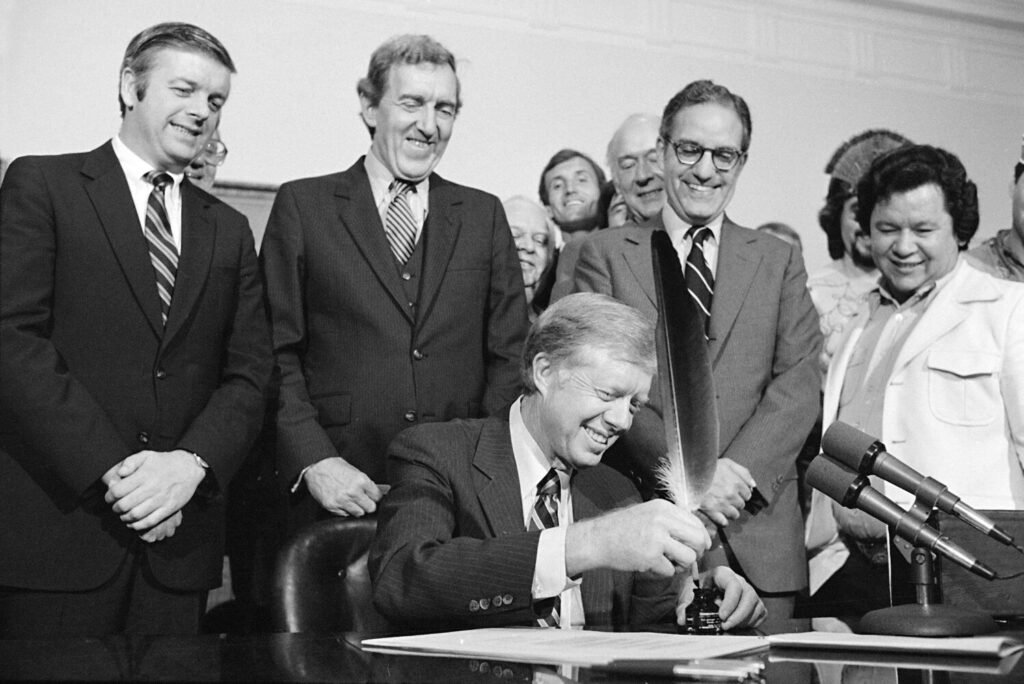 President Jimmy Carter uses an Indian quill pen to sign  the Maine Indian Claims Settlement Act of 1980 at a ceremony at the White House on Oct. 10, 1980.  From left to right are: Maine Gov. Joseph Brennan, Secretary of State Edmund Muskie, Secretary of the Interior Cecil Andrus, Maine Sen. George Mitchell, and Terrance Polchies, a leader of the Association of Aroostook Indians.