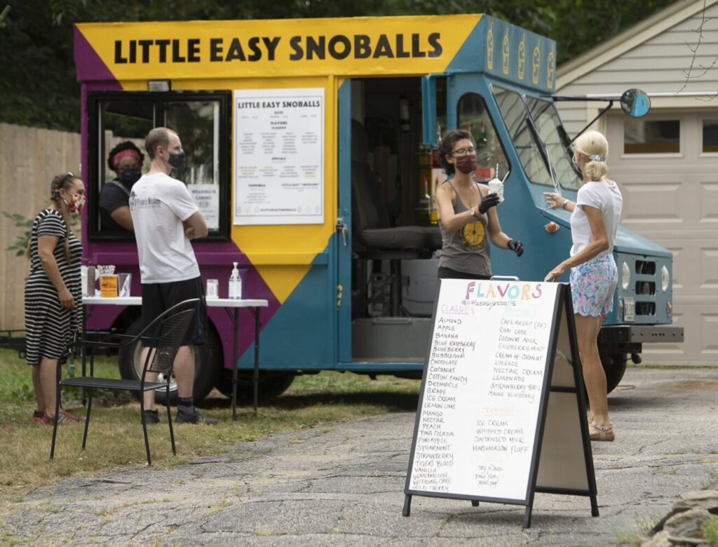 Cassie Pruyn, right, serves a Snoball to a customer during a pop-up event at her home in Portland in early August. This style of shaved ice comes from Louisiana.