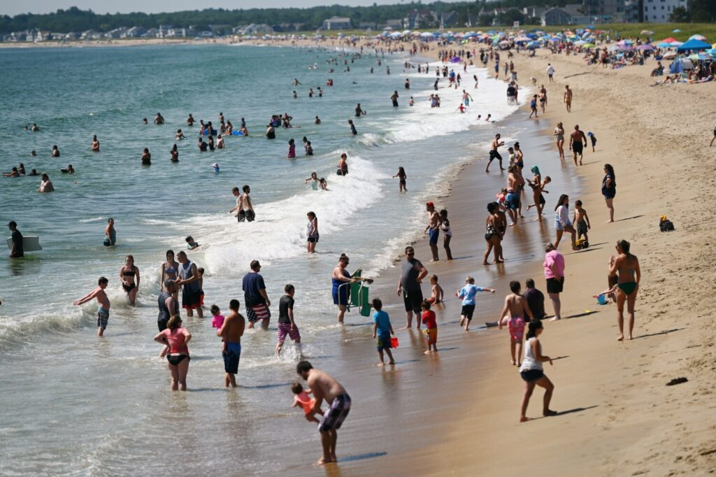 Crowds of people cool off on a hot August day on the beach in Old Orchard Beach.
