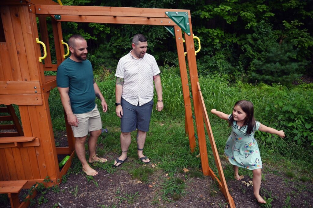 Michael DeFrancisco and his partner Matthew Leavitt watch as their daughter Raenah Defrancisco 6, runs around a swing set outside their Windham home Thursday. Michael and Matthew are looking for other families to join a pandemic pod with theirs for the upcoming school year.