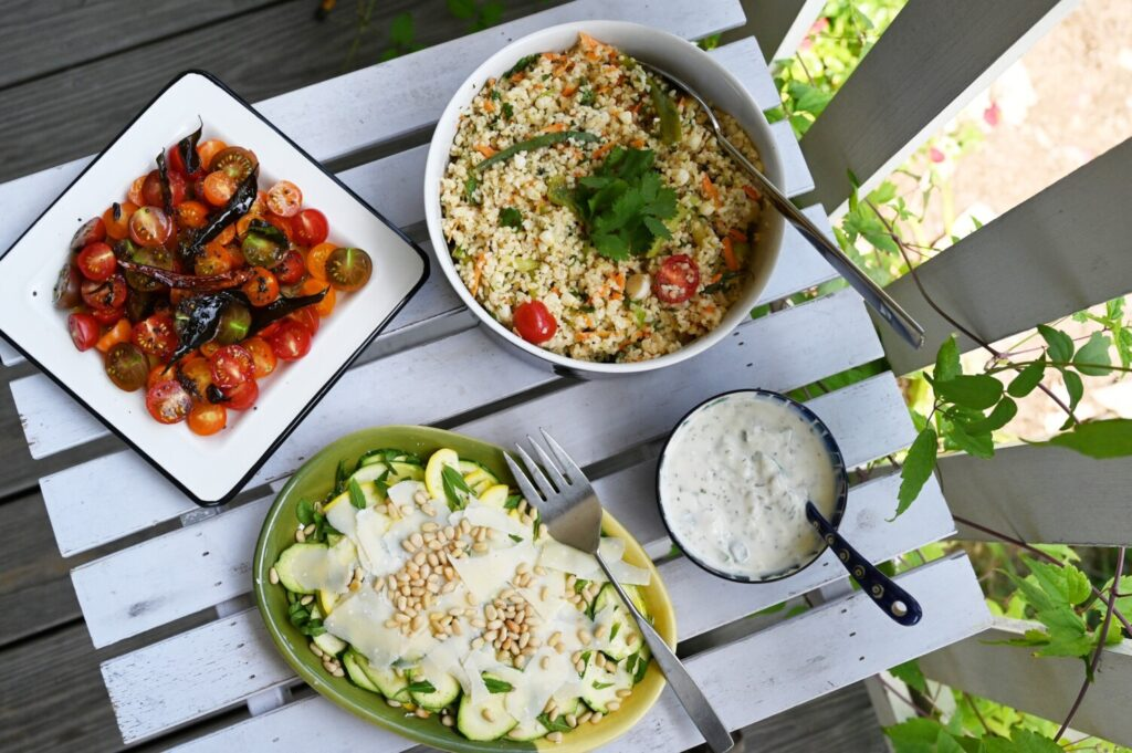 Cooking to beat the heat. Clockwise from top left, Cherry Tomato Salad with Curry Leaves; Everything-But-the-Kitchen-Sink Bulgur Salad; Cucumber Salad with Yogurt, Golden Raisins, Walnuts & Mint; and Shaved Zucchini Salad.