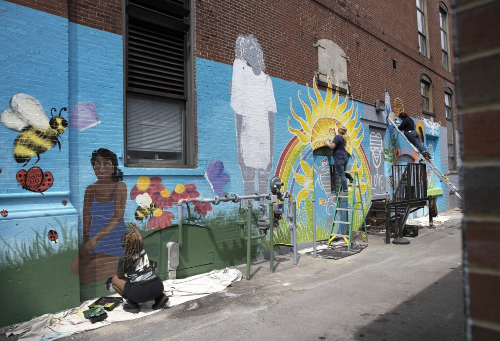 Candice Gosta, left, Karrin Parkinson and Sidney Sanchez, right, work on mural on the backside of 50 Monument Square in Portland on Sunday. (Derek Davis/Staff Photographer)