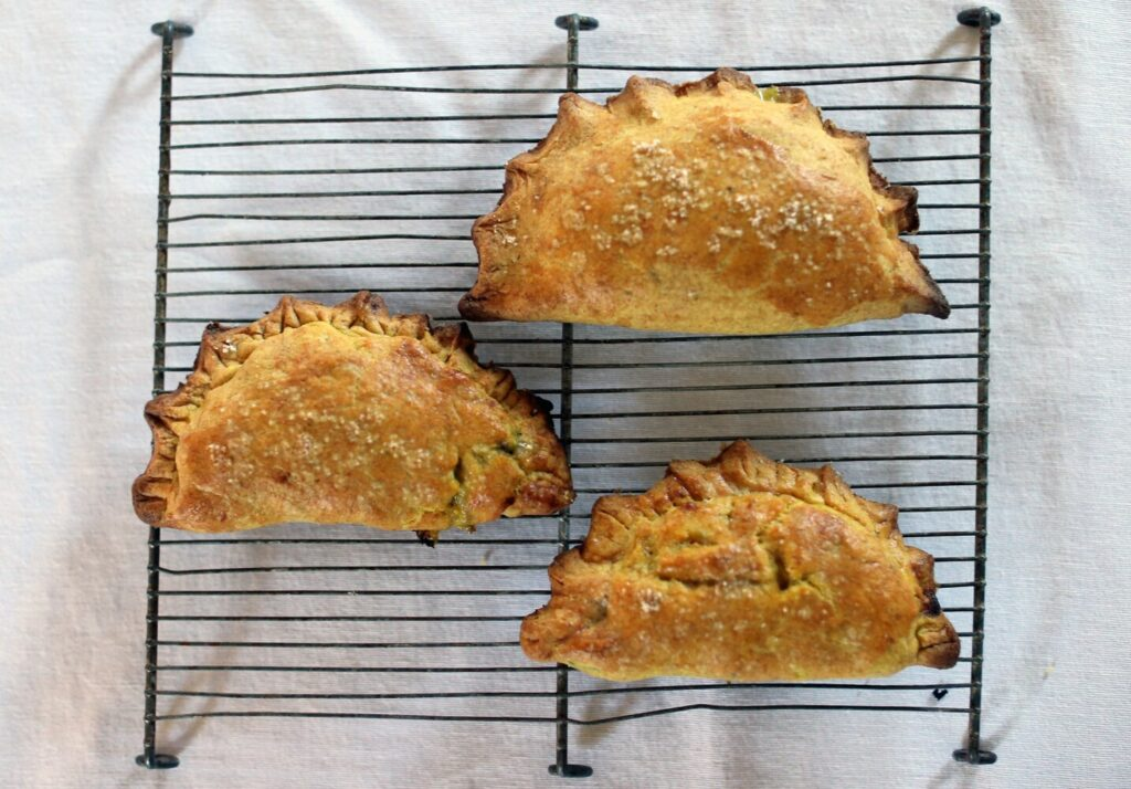 Curried local-vegetable hand pies cool on a cooling rack.
