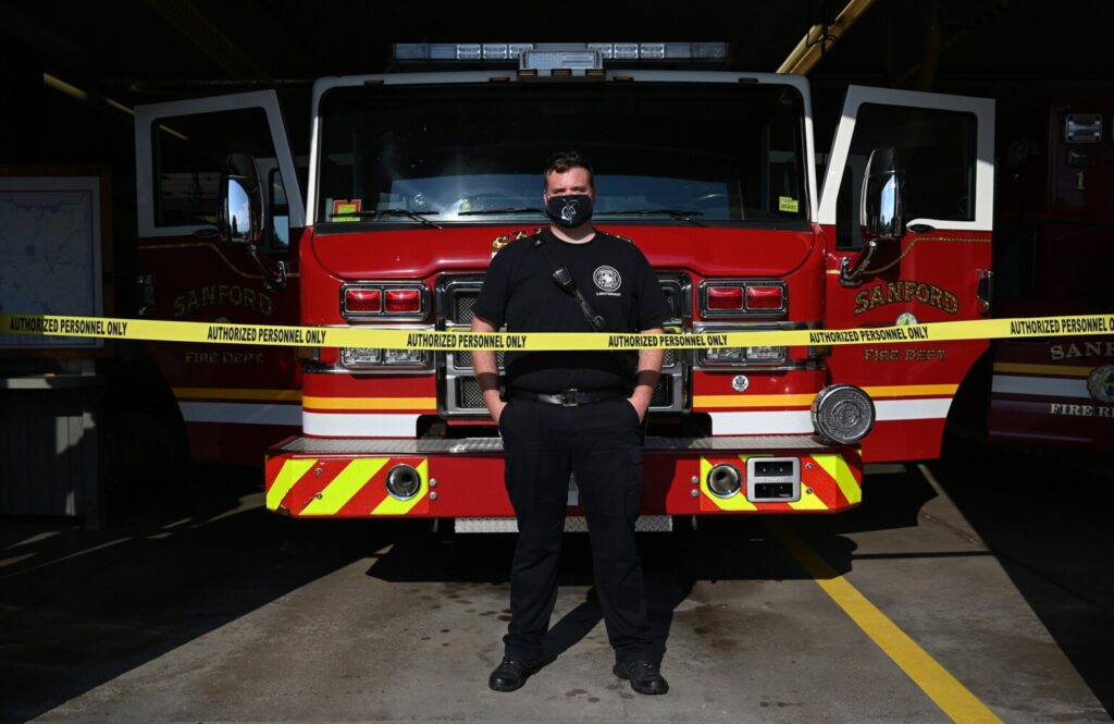 """Sanford firefighter and union President Eric Beecher, shown at the Sanford Fire Department on Monday, said, """"The CDC needs to have a critical status on getting tests completed for critical first responders."""" The police tape, to prevent visitors from walking into the fire station, was up before members of the department tested positive for COVID-19."""