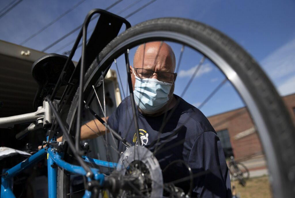 Norman Patry, owner of Summer Feet Cycling in Portland, readies a bicycle for a customer on Wednesday. Hundreds of Maine small businesses and nonprofits applied for state grants this week to support them during the coronavirus pandemic's economic downturn.