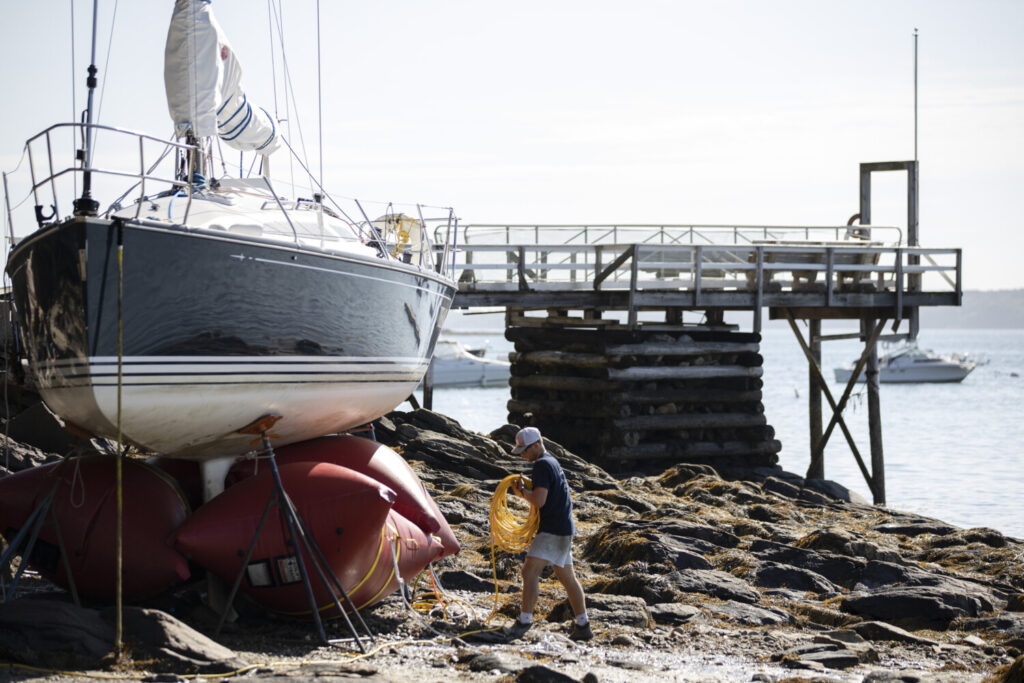 Henry Norris works to stabilize a sailboat that washed ashore in Falmouth overnight as the remnants of Hurricane Isaias blew through Maine. Norris was working with Determination Marine, a company that specializes in salvaging boats, and planned to float the boat back out at high tide on Wednesday.