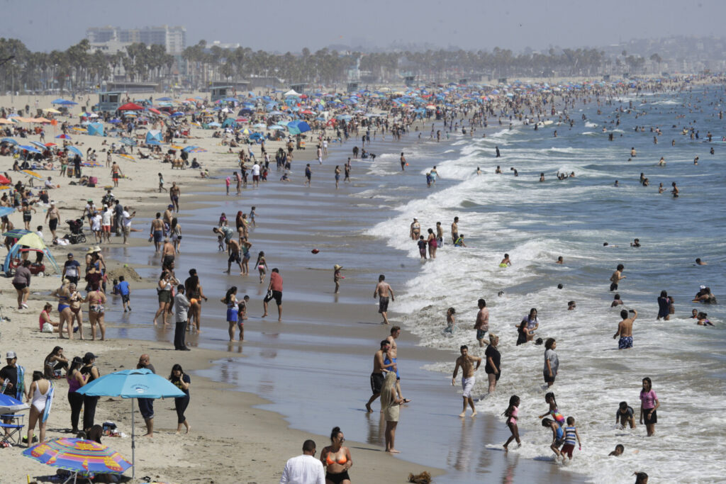 Visitors crowd the beach in Santa Monica, Calif., amid the coronavirus pandemic on July 12. The state faces a heat wave that could bring dangerously high temperatures throughout the state, along with the threat of wildfires and spreading coronavirus infections as people flock to beaches and recreation areas.