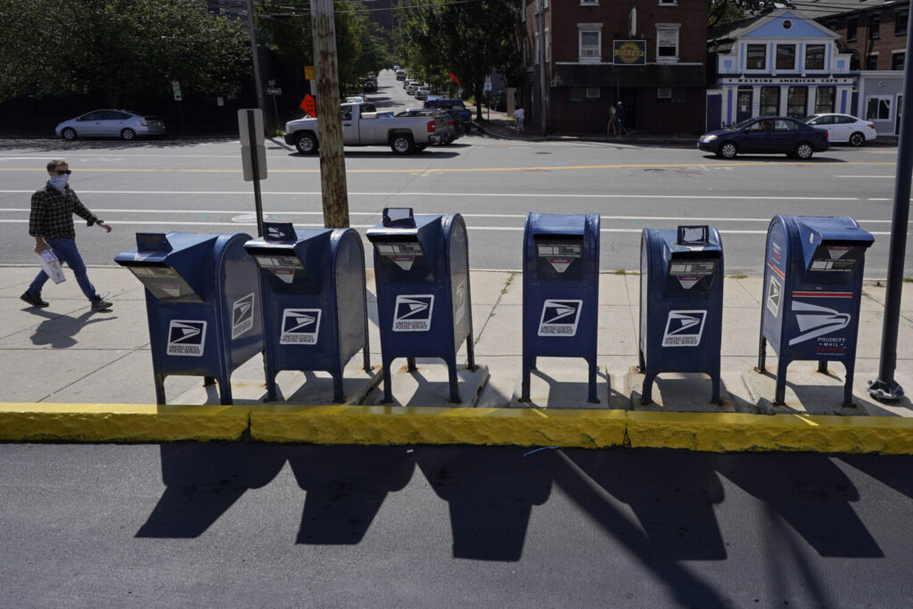 A man walks by a row of U.S. Postal Service mailboxes on his way to the post office, Tuesday, Aug. 18 in Portland.