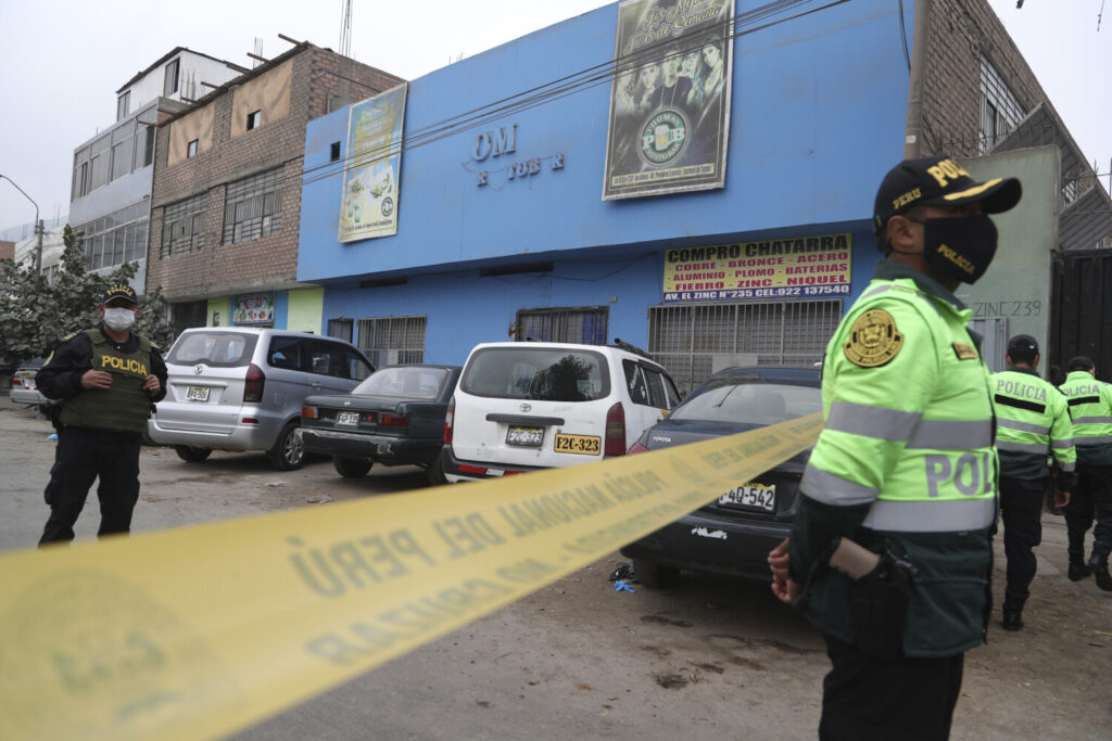 Police officers guard the perimeter of the Tomas Restobar disco in Lima, Peru, where officials say 13 people died on Sunday in a stampede after a police raid to enforce the country's lockdown restrictions.
