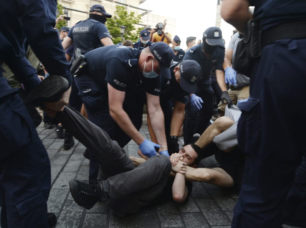 Police scuffle with pro-LGBT protesters angry at the arrest of an LGBT activist in Warsaw, Poland on Friday.