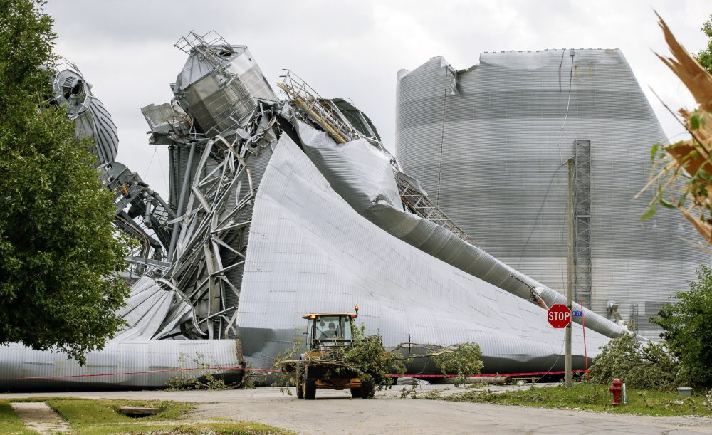 Iowa Department of Transportation workers help with tree debris removal as grain bins from the Archer Daniels Midland facility are seen severely damaged in Keystone, Iowa, on Wednesday. A storm slammed the Midwest with straight line winds of up to 100 miles per hour on Monday, gaining strength as it plowed through Iowa farm fields, flattening corn and bursting grain bins still filled with tens of millions of bushels of last year's harvest.